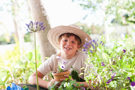 cropped out: Boy potting plants outdoors