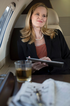 access point: Businesswoman using tablet on airplane LANG_EVOIMAGES