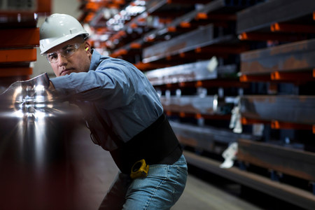 engrossed: Worker using machinery in metal plant LANG_EVOIMAGES