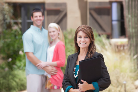 Realtor with couple outside home LANG_EVOIMAGES