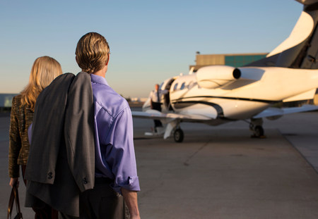 affluent: Business people on airplane runway