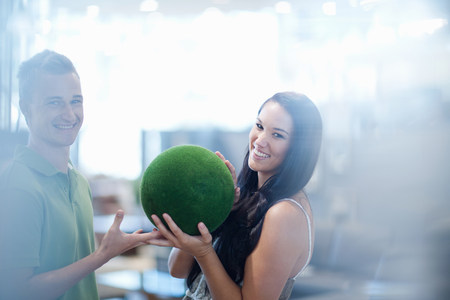 customer facing: Smiling couple holding green ball LANG_EVOIMAGES