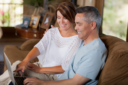indicate: Couple using laptop together on sofa