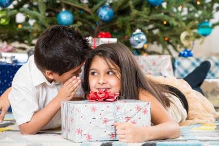 Children whispering by Christmas tree