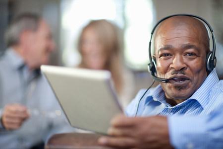 technology: Older man wearing headset LANG_EVOIMAGES