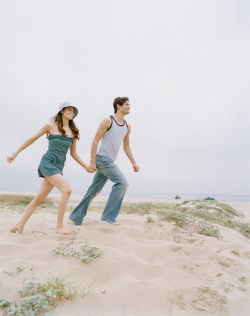 Couple walking together on beach LANG_EVOIMAGES