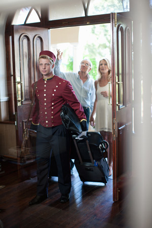 bellhop: Bellhop carrying luggage in hotel