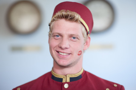 Bellhop smiling with kiss print on cheek