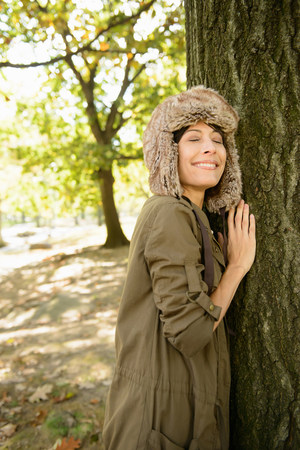 Smiling woman hugging tree in park LANG_EVOIMAGES