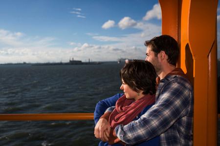 ponderous: Couple hugging on ferry in urban harbor