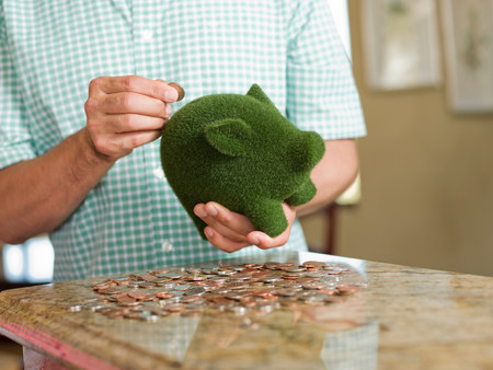 Man putting coins in green piggy bank LANG_EVOIMAGES