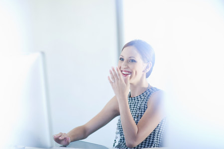 giggling: Businesswoman laughing at desk LANG_EVOIMAGES