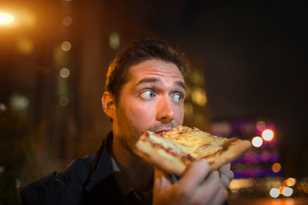 off shoulder: Man eating pizza on city street