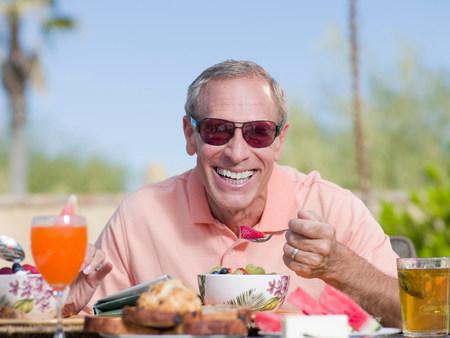 Older man having breakfast outdoors