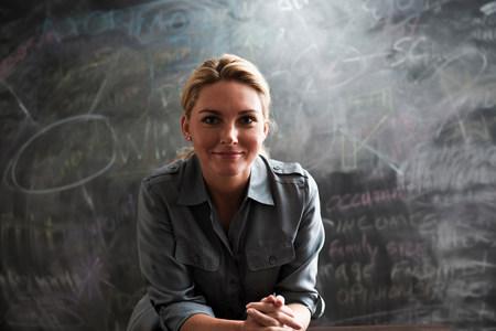 fair haired: Portrait of woman in front of blackboard