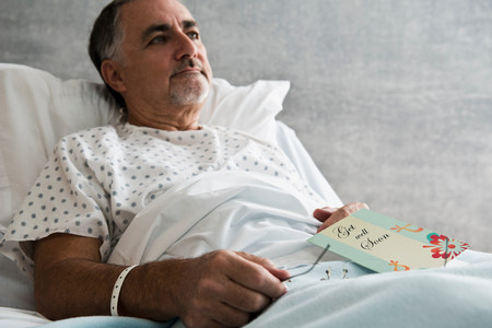 Male hospital patient with get well soon card