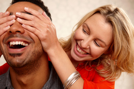 obscuring: Woman covering boyfriends eyes LANG_EVOIMAGES