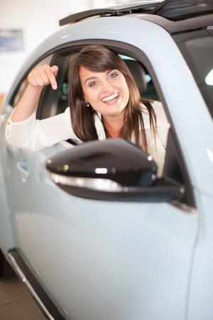 indicate: Excited woman pointing to new car LANG_EVOIMAGES
