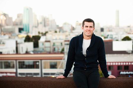 negative area: Smiling man sitting on urban balcony