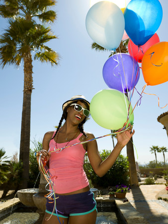 Woman holding bunch of balloons outdoors LANG_EVOIMAGES