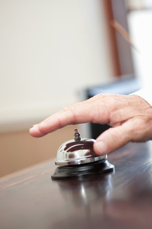 Man ringing bell in hotel lobby