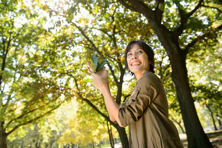 tilting: Woman playing with leaves in park LANG_EVOIMAGES