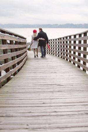 embraced: Couple walking on wooden dock