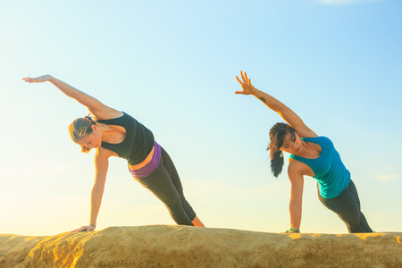 Women practicing yoga on rock formation LANG_EVOIMAGES