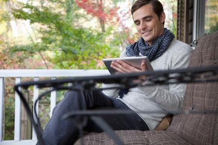 Mann mit Tablet-Computer auf der Veranda LANG_EVOIMAGES