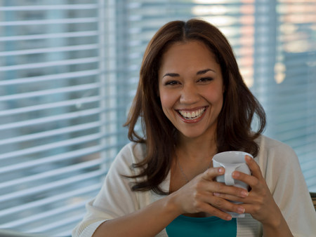 headshots: Smiling woman having cup of coffee LANG_EVOIMAGES