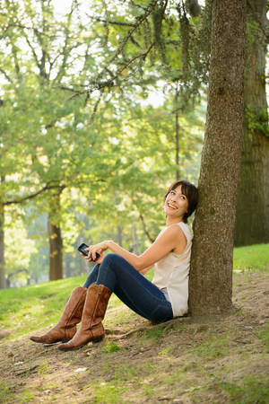 Woman using cell phone in park