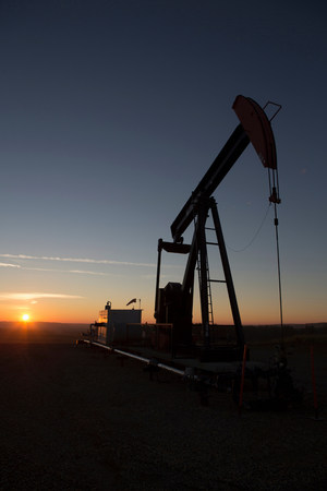 Silhouette of oil well in dry landscape LANG_EVOIMAGES