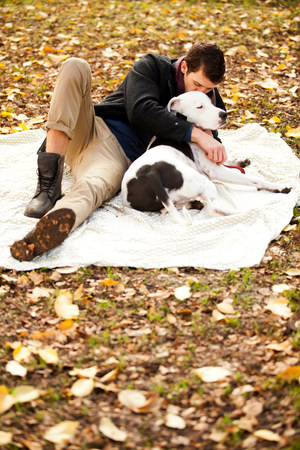 Man and dog relaxing on picnic blanket LANG_EVOIMAGES