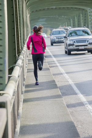 negative area: Woman running on urban bridge