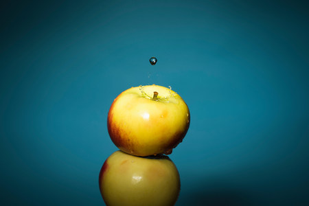 mirroring: Close up of water splashing on apple