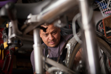 engrossed: Mechanic working in bicycle shop LANG_EVOIMAGES