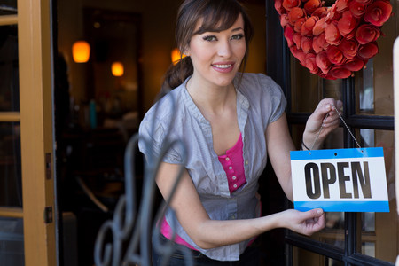 proudly: Woman hanging open sign on door