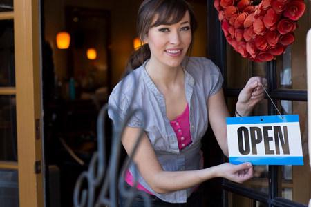 assured: Woman hanging open sign on door