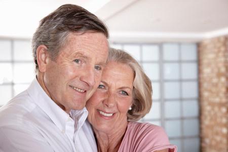 buen vivir: Pareja mayor abrazos en la sala de estar