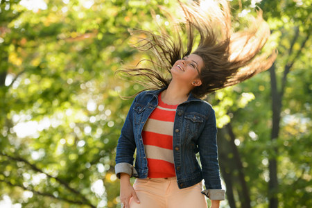Woman tossing her hair in park LANG_EVOIMAGES