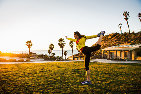 energy work: Woman practicing yoga on green lawn