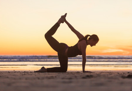 Woman practicing yoga on beach LANG_EVOIMAGES