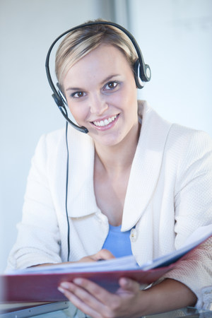 Businesswomen wearing headset at desk LANG_EVOIMAGES