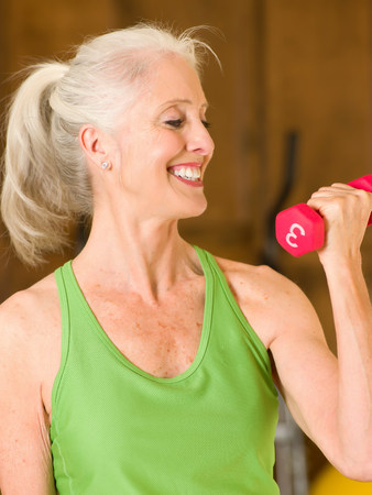 Older woman lifting weights at home