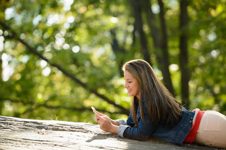 check ups: Woman using cell phone in park