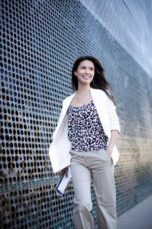 assured: Smiling businesswoman walking outdoors