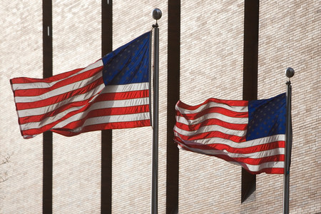 high winds: American flags flying by skyscraper LANG_EVOIMAGES