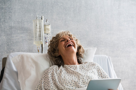 recuperating: Female hospital patient with digital tablet,laughing LANG_EVOIMAGES