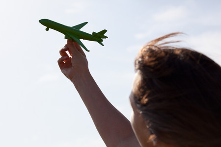 woman hanging toy: Woman playing with toy airplane LANG_EVOIMAGES