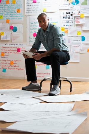 businessman pondering documents: Man sitting on stool with digital tablet LANG_EVOIMAGES